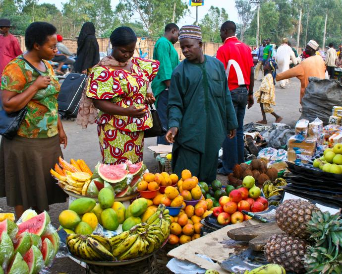 Shoppers stand at stall in Nigerian fruit market