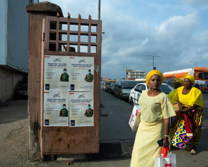 Two women in Lagos, Nigeria carry food and supplies past signs about COVID-19